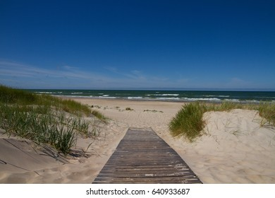 Wooden footpath leading to the Baltic Sea with waves in a bright summer windy day