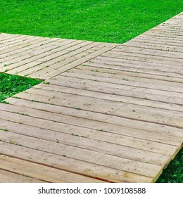 Wooden Footpath Made From Unpainted Pine Boards On The Fresh Lawn, Close Up