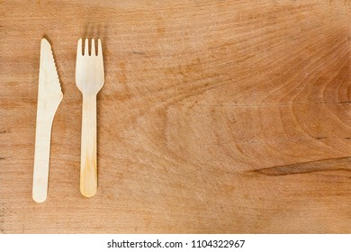 Wooden fork and knife on a wooden background from above. Studio shot. Kitchen utensil.