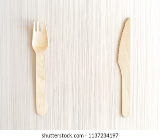 Wooden fork and spoon on a neutral background.
