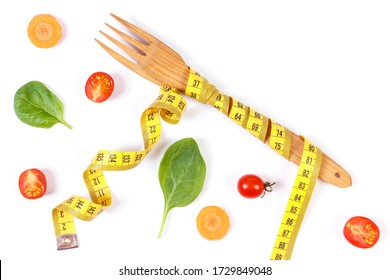 Wooden fork wrapped in tape measure and fresh ripe vegetables on white background, concept of lose weight and healthy nutrition