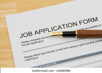 A wooden fountain pen on a wooden desk with a job application form, Applying for a job