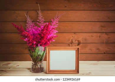Wooden frame and beautiful astilbe flowers in glass vase on wooden table. View with copy space.