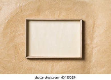 Wooden Frame over Paper Background, Empty Wood Border for Picture on Brown Papers Texture