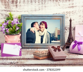 Wooden Frame with picture of young couple and romantic accessories with gift boxes on wooden background. Selective focus.