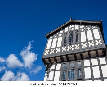 Wooden framed black and white mock Tudor building with Gabled overhang.