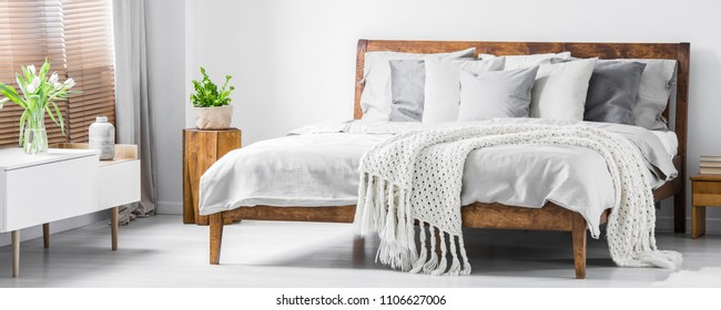 Wooden framed comfortable bed with many pillows, blanket and sheets and a sideboard with flowers on top in a white stylish bedroom interior. Real photo. Panorama.