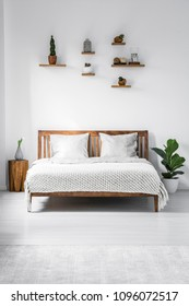 Wooden framed double bed with two pillows and a blanket, and small shelves above in a white bedroom interior. Real photo.