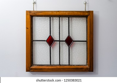 Wooden framed English stained glass window with red diamond pattern glass hanging by chains on a white wall