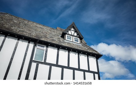 Wooden framed mock Tudor building with small attic gabled window.