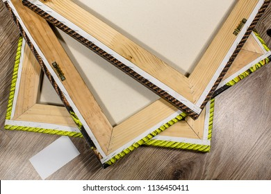 Wooden frames with stretched canvas and white blank card on a floor.