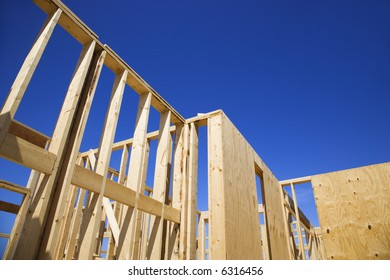 Wooden framework of new construction with blue sky in background.