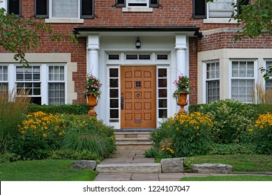 wooden front door of home with elegant portico entrance and  flowers