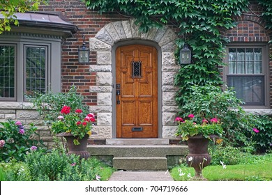 wooden front door of house with ivy and flower pots