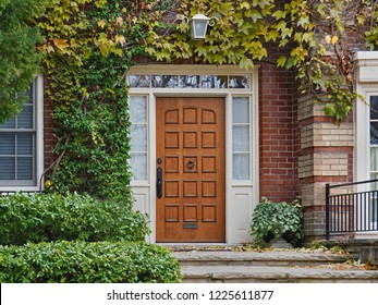 Wooden front door of house surrounded by vines