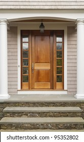 Wooden Front Door showing pillars and arch entrance. Also shows three steps leading to entrance.