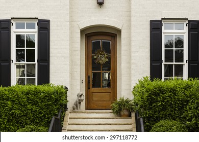 Wooden front door of a traditional style home with brick accents.