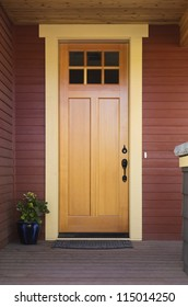 Wooden front door of an upscale home. View of a wooden front door on a red house with black accents. Vertical shot.
