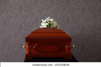 Wooden funeral casket with white lilies at grey wall