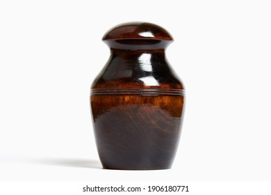 Wooden funeral urn of pet, isolated white background. Burial cinerary urn close up.
