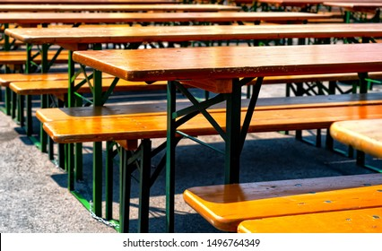 Wooden furniture in a beer garden , tables and benches, empty,