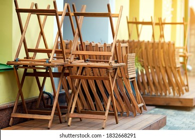 Wooden furniture folded on summer terrace before the opening of the restaurant. Street cafe before opening. Pile of wooden chairs and tables on summer terrace of street cafe