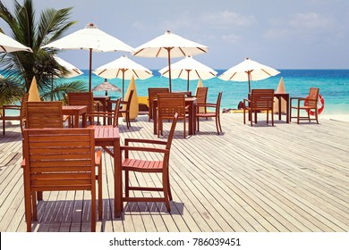 Wooden furniture with tables and chairs on terrace, sunshade umbrellas on sea view background, outside and no people, toned image