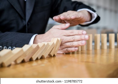 Wooden game strategy, Businessman hand stopping falling wooden dominoes effect from continuous toppled or risk and protection, strategy and successful intervention concept for business.