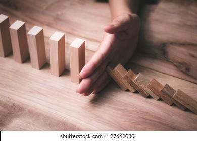 Wooden game strategy, Businessman hand stopping risk falling wooden dominoes effect Create stability for the company
