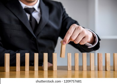 Wooden game strategy, Risk and strategy in business, Close up of businessman hand gambling placing wooden block on a line of domino.