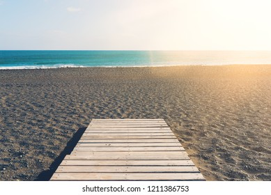 wooden gangplank on beach against sea and blue sky on sunny day