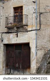 wooden garage door and balcony above in old facade