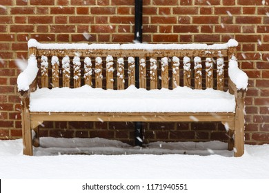 Wooden garden bench covered in snow against a brick wall