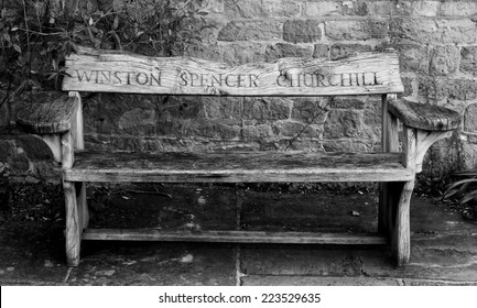 Wooden garden bench with the name Winston Spencer Churchill carved in the back from Chartwell House, Kent, his home until he died in 1965.  Against a stone wall on stone flagging.  Black and white .