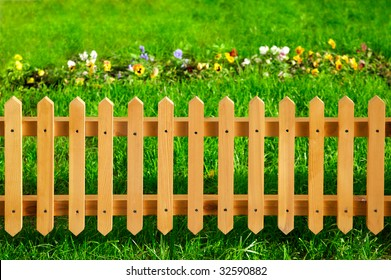 Wooden garden fence against green grass and flowers