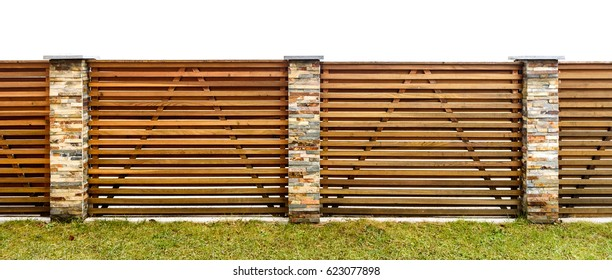 Wooden garden fence with stone paved pillars guarding private property. Fence made of horizontal wooden planks and backyard lawn.