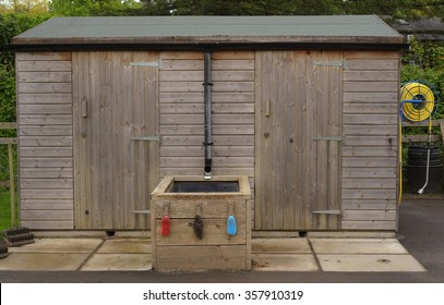 Wooden Garden Shed with a Hose Reel Attached at One End and Brushes for Cleaning Garden Tools in Devon, England, UK