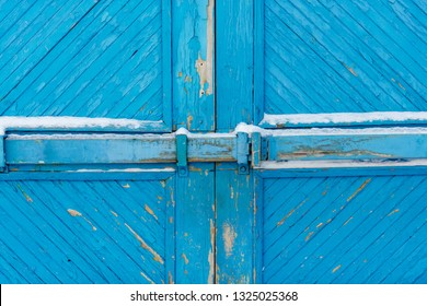 Wooden gate covered with white snow. Blue colored pattern of planks. Door closed on old bolt.