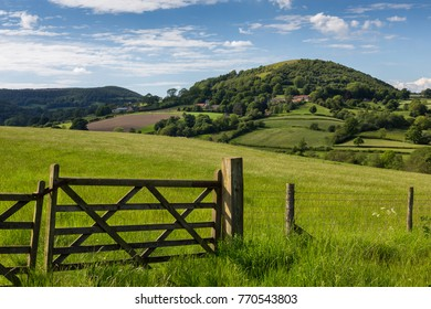 A wooden gate and fence in a field with Hawnby in the background in the North York Moors National Park.
