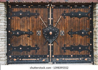 Wooden gates with forged hinges. A shield and a sword hang on the gate.