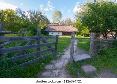 wooden gateway to the courtyard with a white, authentic home garden near the garden. Uzhhorod Ukraine