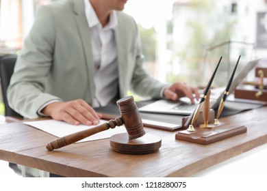 Wooden gavel and blurred notary with laptop on background