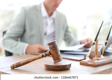 Wooden gavel and blurred notary on background