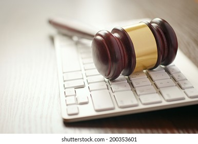 Wooden gavel with a brass decoration lying on a computer keyboard conceptual of online auctions or law enforcement