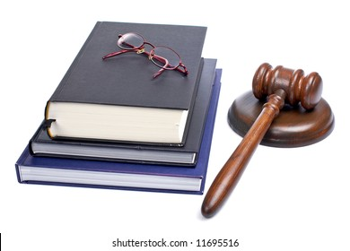 Wooden gavel from the court, glasses and law books isolated on white background. Shallow depth of field