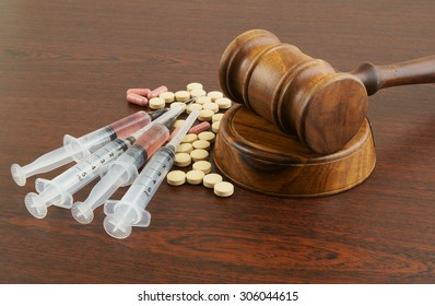 Wooden gavel with drugs and syringes on table