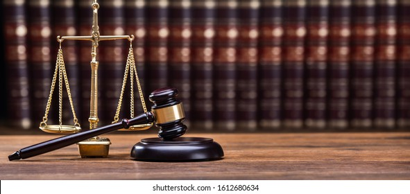 Wooden Gavel With Golden Scale On Table