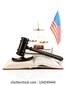 Wooden gavel, golden scales of justice, books and American flag isolated on white