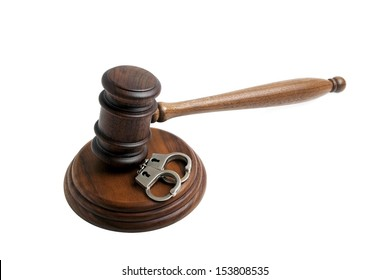 Wooden gavel and handcuffs, isolated on white background