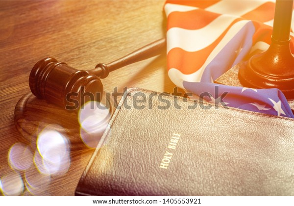 Wooden gavel and holy black bible with American flag